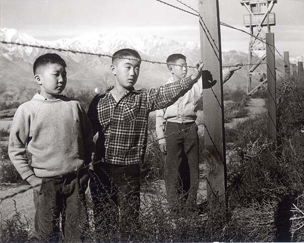 Three boys looking through barbed-wire camp fence - Toyo Miyatake