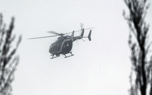 A helicopter with members of the French intervention gendarme forces hover above the scene of a hostage taking at an industrial zone in Dammartin-en-Goele, northeast of Paris