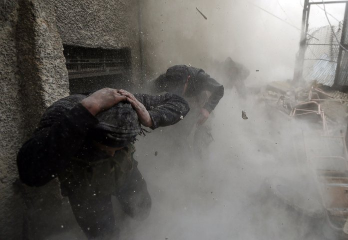 Free Syrian Army fighters run for cover as a tank shell explodes on a wall during heavy fighting in the Ain Tarma neighbourhood of Damascus Foto: Goran Tomasevic