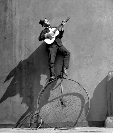 "Ken Russell ""Man on bike playing guitar"" [1956]"